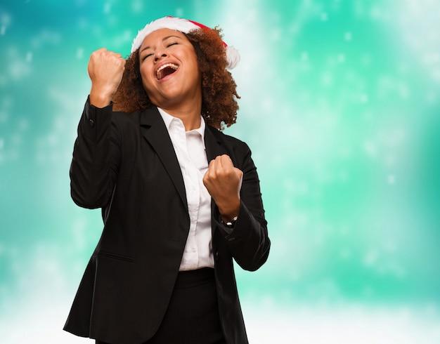 Молодой бизнес черная женщина в шляпе санта-клауса, который не сдается
