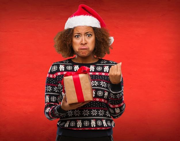 クリスマスの日に必要なジェスチャーをしている贈り物を保持している若い黒人の女性