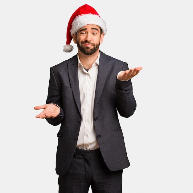混乱して疑わしいサンタの帽子を身に着けている若いビジネスマン