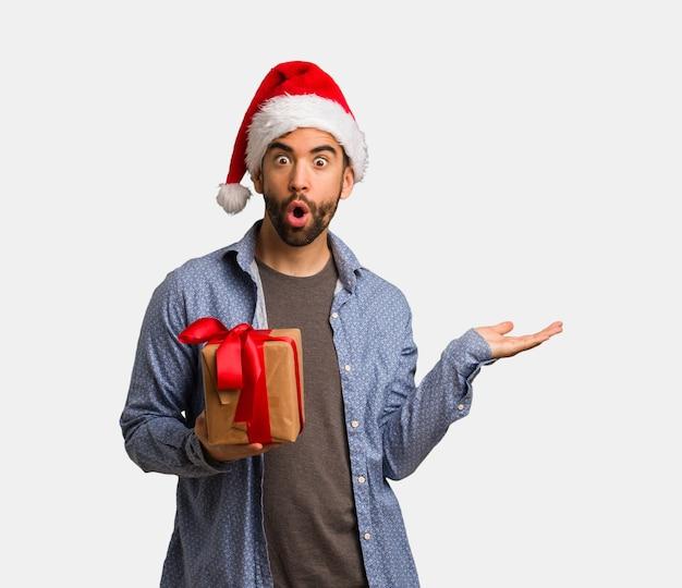 Молодой человек в шляпе санта держит что-то на ладони