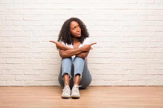 木製の床に座っている若い黒人の女性は、混乱し疑いのある男