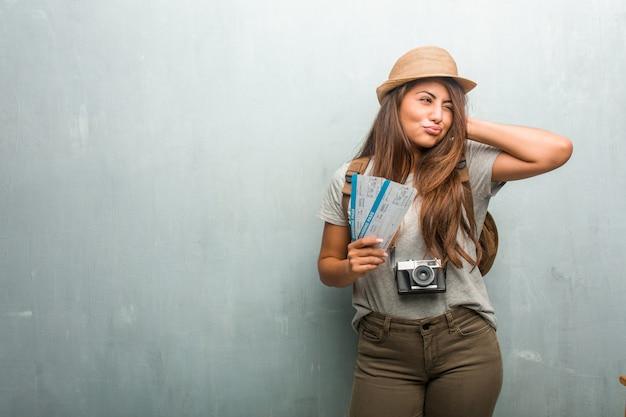 Портрет молодой путешественницы латинской женщины против настенного покрытия уши руками