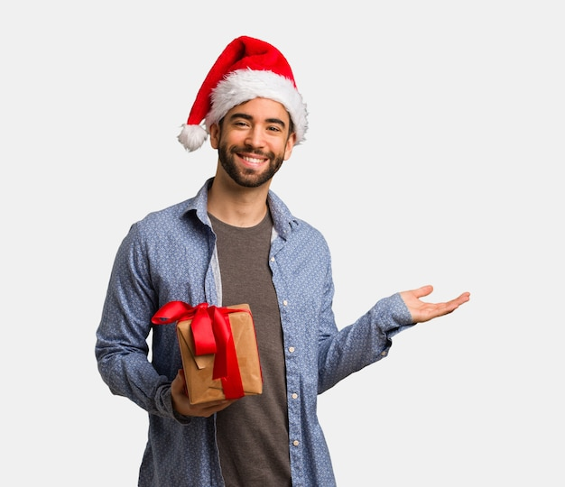 手で何かを保持しているサンタの帽子を着ている若い男