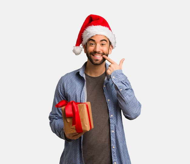 Молодой человек в шляпе санта улыбается, указывая рот