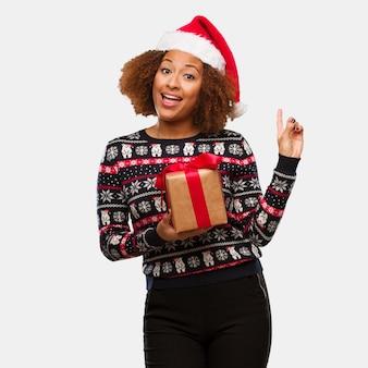 クリスマスの日に指で側を指している贈り物を保持している若い黒人の女性