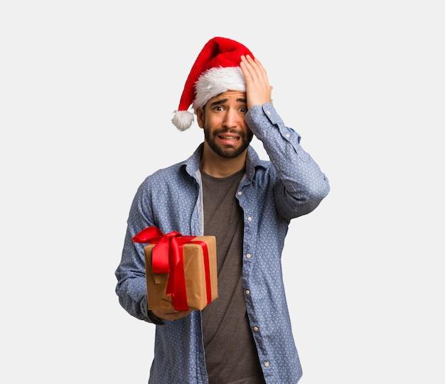 Молодой человек, носящий шляпу санта забывчивым, реализовать что-то