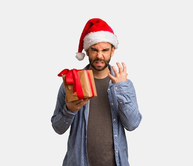 サンタの帽子を着た若い男は怒っていて怒っている