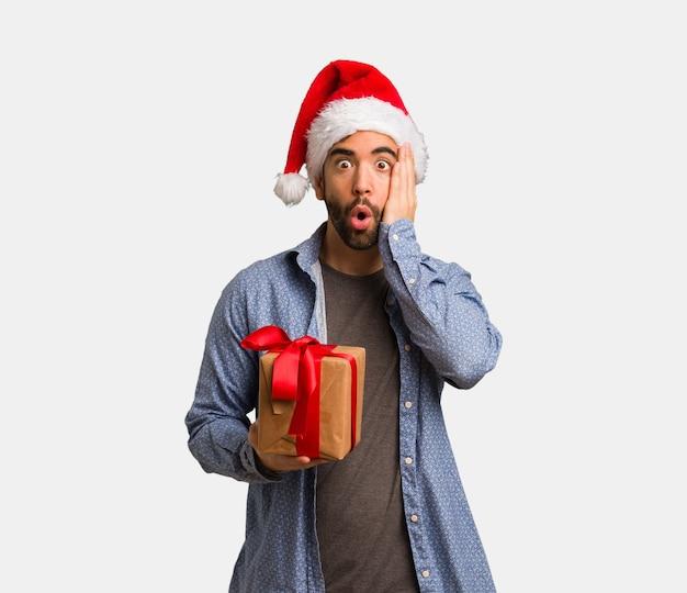 サンタの帽子を着た若い男は驚いてショックを受けました