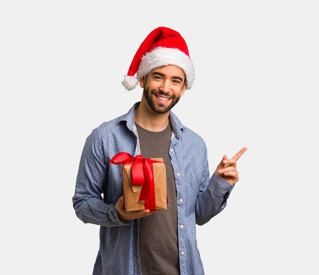 笑顔と側を指しているサンタの帽子を身に着けている若い男