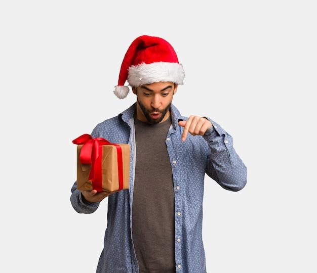 下を指しているサンタの帽子を着て若い男