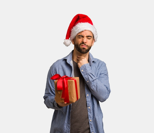サンタの帽子を着た若い男は、咳、病気のためにウイルスや感染症