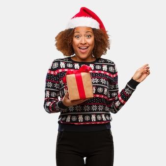 手で何かを保持してクリスマスの日に贈り物を保持している若い黒の女性