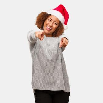 明るい、笑顔の、サンタの帽子を身に着けている若い黒人の女性