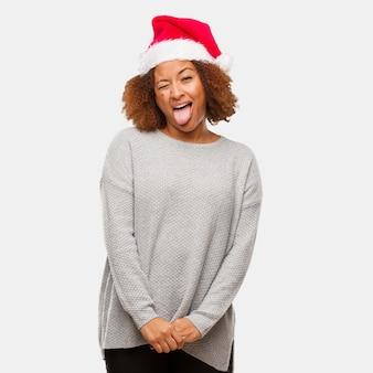 若い黒の女性は、サンタの帽子をかわいいと舌を見せてくれる