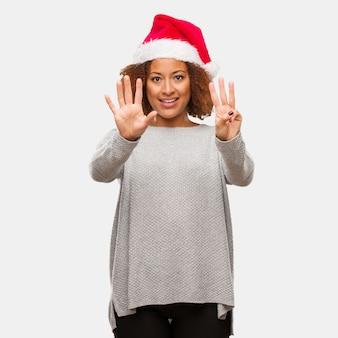 Молодая негритянка в шляпе санта показывает номер восемь