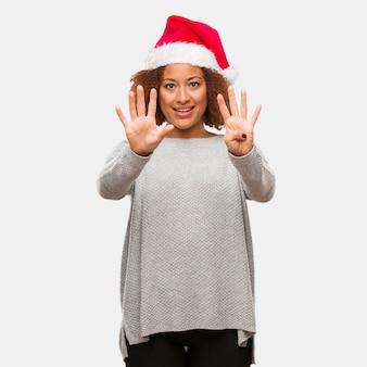 Молодая негритянка в шляпе санта показывает номер девять