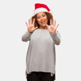 Молодая чернокожая женщина в шляпе санта показывает номер десять
