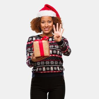 Молодая негритянка держит подарок в рождество, показывая номер четыре