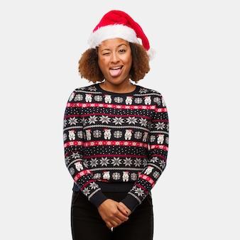 プリントファニーとフレンドリーな舌を表示してトレンディなクリスマスセーターの若い黒人の女性