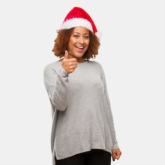 笑顔と親指を上げるサンタの帽子を身に着けている若い黒人の女性