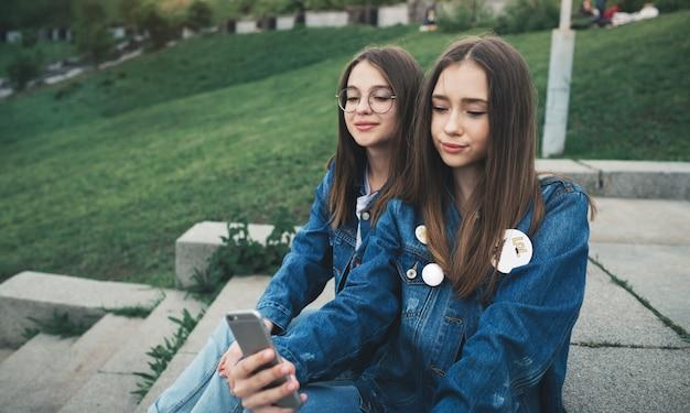 Портрет молодых друзей, принимая автопортрет с телефоном в городском парке