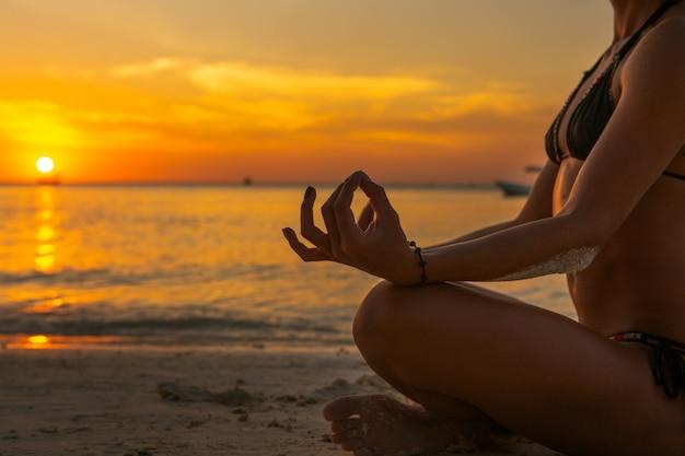 Женщина делает медитации на пляже на закате