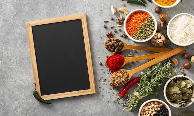 米、さまざまな豆とスパイスとハーブのトップビューで空白の黒板