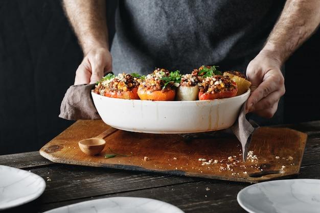調理された詰めピーマンを保持している男性の手健康的なベジタリアン料理