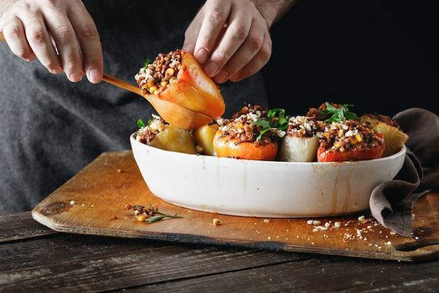 Мужские руки, держа приготовленные фаршированные перцы здоровое вегетарианское питание