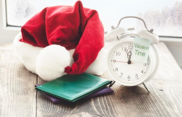 休暇時間は、クリスマスのコンセプトに旅行します。ウィンドウに対して木製テーブルの上のメモ、パスポート、サンタクロースの帽子とビンテージの目覚まし時計