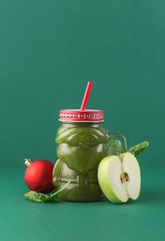 廃棄物ゼロのコンセプト。ガラスサンタクロースの瓶に緑の背景に青リンゴほうれん草のスムージー。健康とダイエット食品のコンセプト