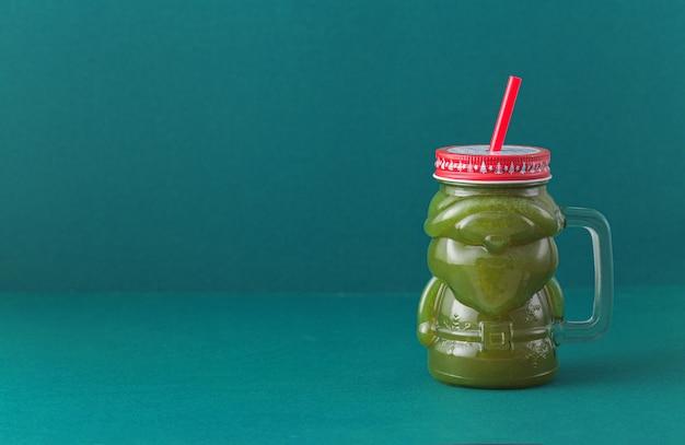 ガラスサンタクロースの瓶にコピースペースを持つ青色の背景に緑の野菜のスムージー。健康的な食事、廃棄物ゼロのコンセプト