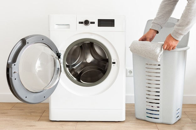 サイドビュー男はバスケットから服を取り出し、家庭用洗濯機に洗濯機を入れて