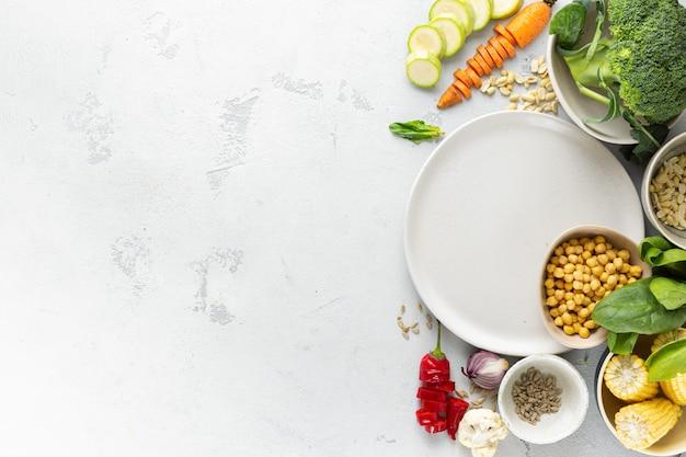 ベジタリアン料理と空のプレート。ビーガンミールトップビューを調理するための新鮮な食材