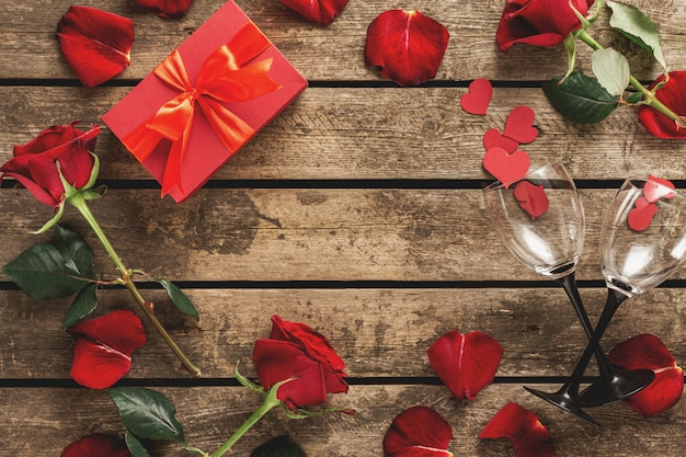 木製テーブルトップビューで花バラの花びらワイングラスとバレンタインの日フレーム赤いギフトボックス