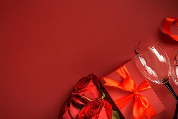 バラの花とワイングラスと赤いギフトボックスとバレンタインデーの背景