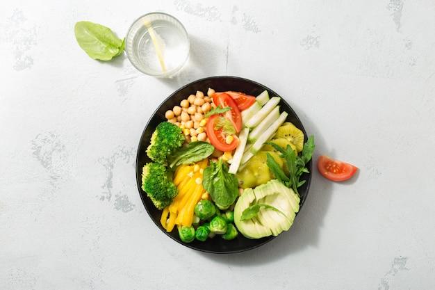 Концепция здорового питания диетолога. полезный овощной обед из нута, брокколи, перца, помидоров, шпината, брюссельской капусты, рукколы и авокадо. вид сверху