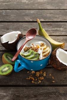 グラノーラとフルーツのおいしいココナッツヨーグルトを素朴な木製のテーブルで提供しています。健康的なビーガンフード。おいしいと健康的な朝食のコンセプト