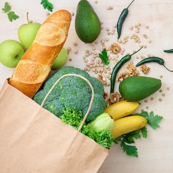 Продуктовый магазинный бумажный пакет со здоровой пищей на деревянном столе