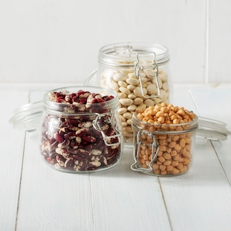 木製のテーブルのガラスの瓶に別の豆のセットです。菜食主義者のためのタンパク質の源。健康的な食事のコンセプト