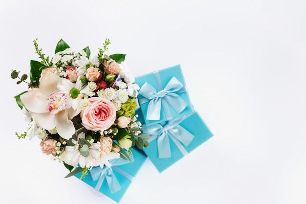 バレンタインデーや母の日のコンセプトです。白い背景の上のギフトと花の花束。フラット横たわっていた、トップビュー花組成