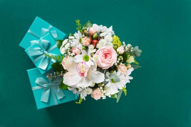 バレンタインデーや母の日のコンセプトです。緑の背景にギフトと花の花束。フラット横たわっていた、トップビュー花組成