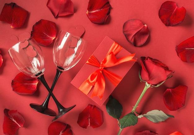 День святого валентина, концепция дня матери красная подарочная коробка с цветами, лепестки роз, бокалы с плоским рельефом