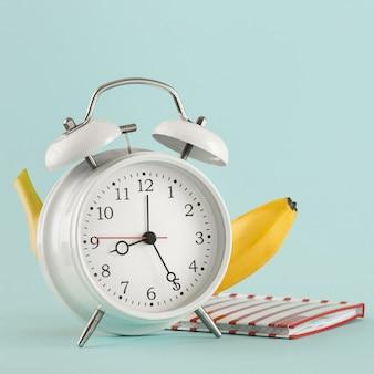 教育の概念古い目覚まし時計バナナメモ帳明るい背景場所テスト