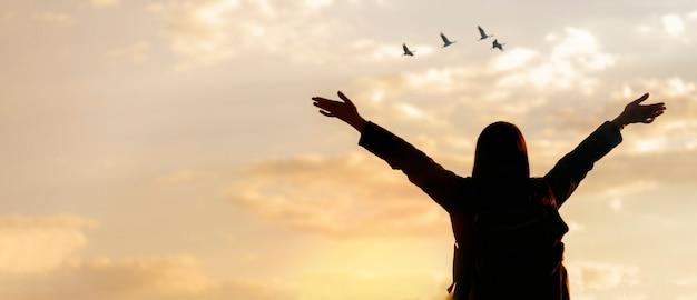 自由の概念。空を探している開いた手で自由を楽しんで幸せな若い女