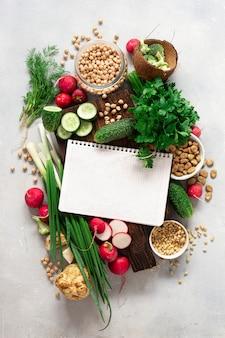 健康的なビーガンフードのコンセプトです。新鮮な野菜、ハーブ、マメ科植物、ナッツの空白のノートブック。野菜料理のコンセプト