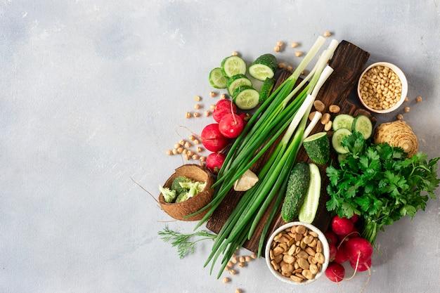 ビーガンメニューのコンセプトです。明るい背景上面にビーガンフードを調理するための食材を使った木製の素朴なまな板