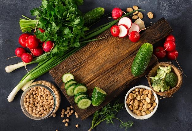 メニュー食品の背景。暗い背景の上面にビーガンフードを調理するための食材を使った木製の素朴なまな板