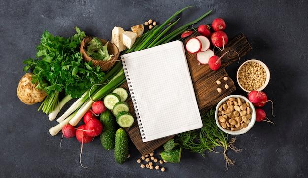 健康的なバランスのとれたビーガンフードのコンセプトです。新鮮な野菜、ハーブ、シリアル、ナッツの空白のノートブック。野菜料理