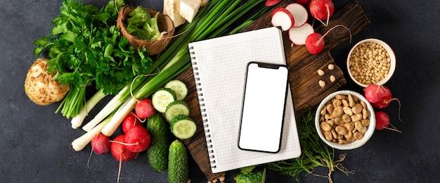 Заказать еду онлайн концепции. смартфон с пустой экран и блокнот с ингредиентами для приготовления веганской пищи. свежие овощи, травы, крупы и орехи на темном фоне вид сверху